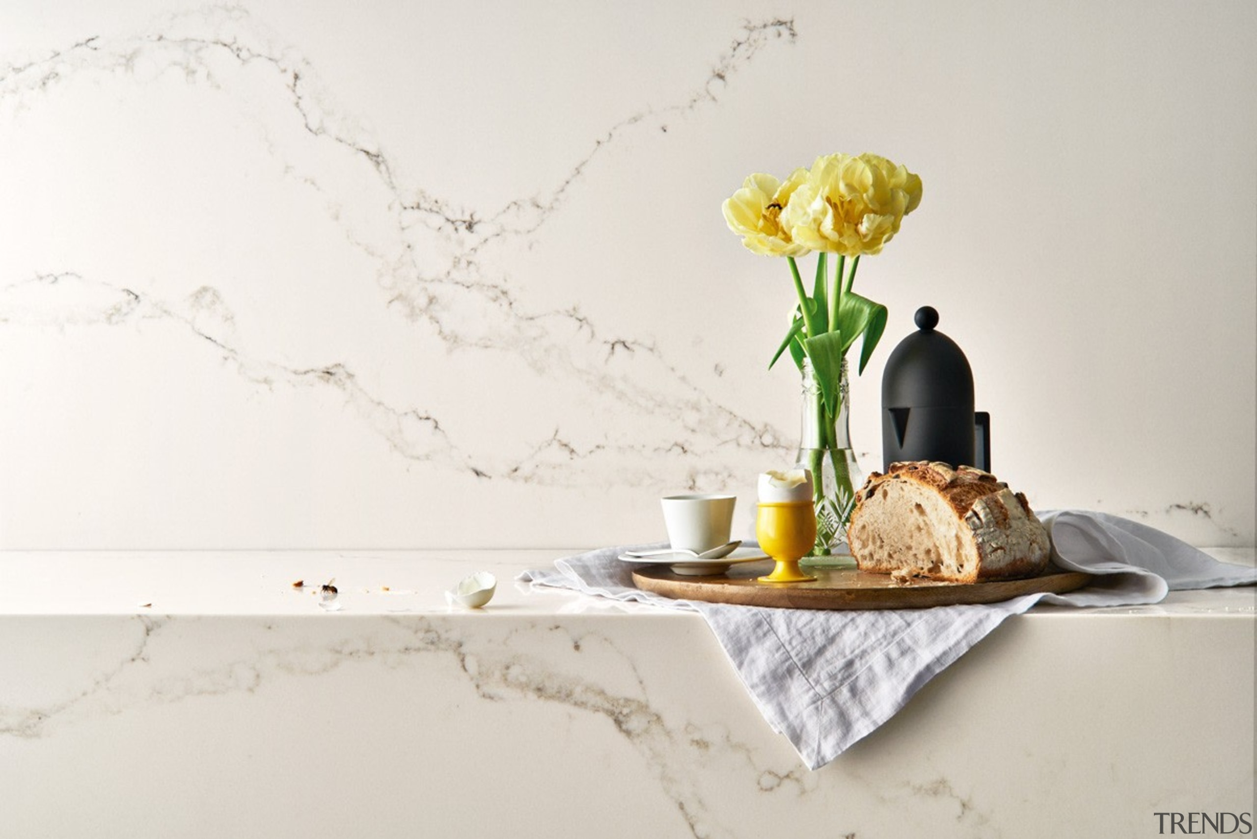 Caesarstone's interpretation of Statuario marble; Statuario Nuvo brings interior design, product design, still life photography, table, vase, yellow, white