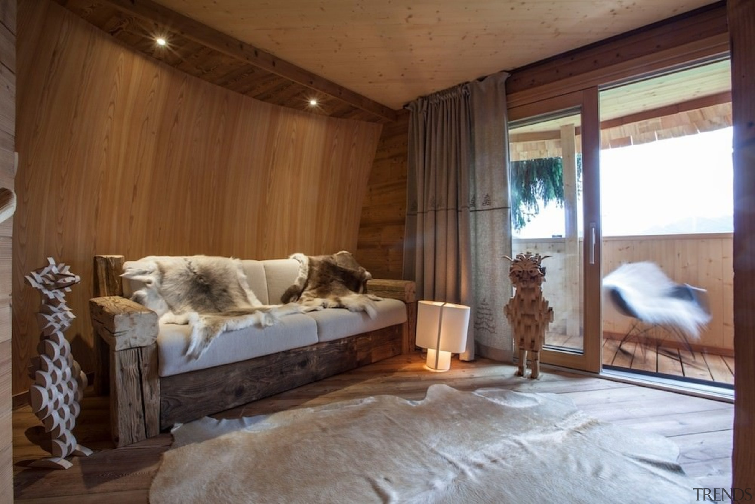 The curved walls reinforce the cozy, cabin-like feel bed, bed frame, bedroom, home, house, interior design, log cabin, property, room, window, wood, brown