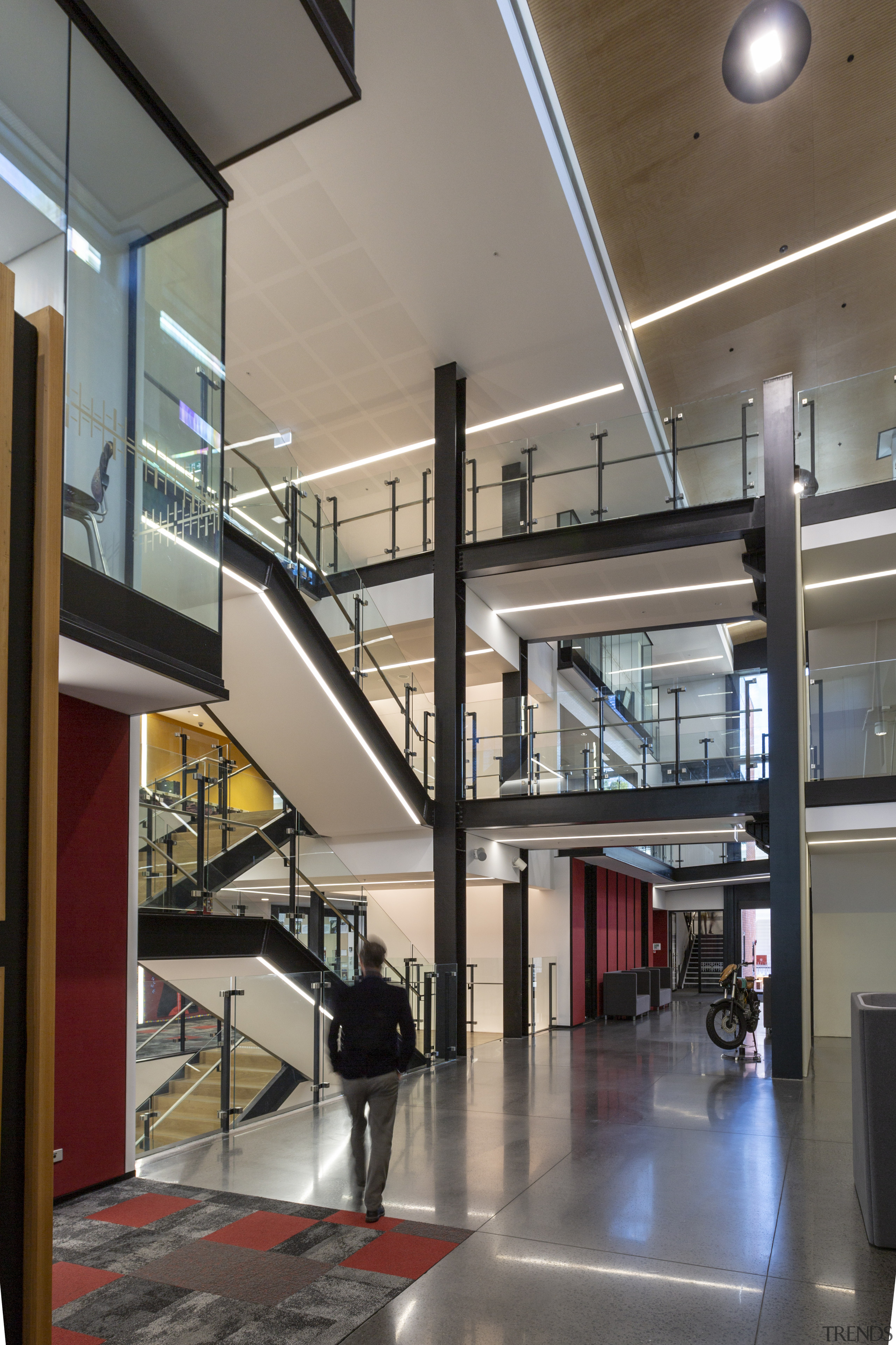 A soaring atrium and pedestrian street intersect in architecture, building, daylighting, glass, handrail, interior design, lobby, stairs, gray
