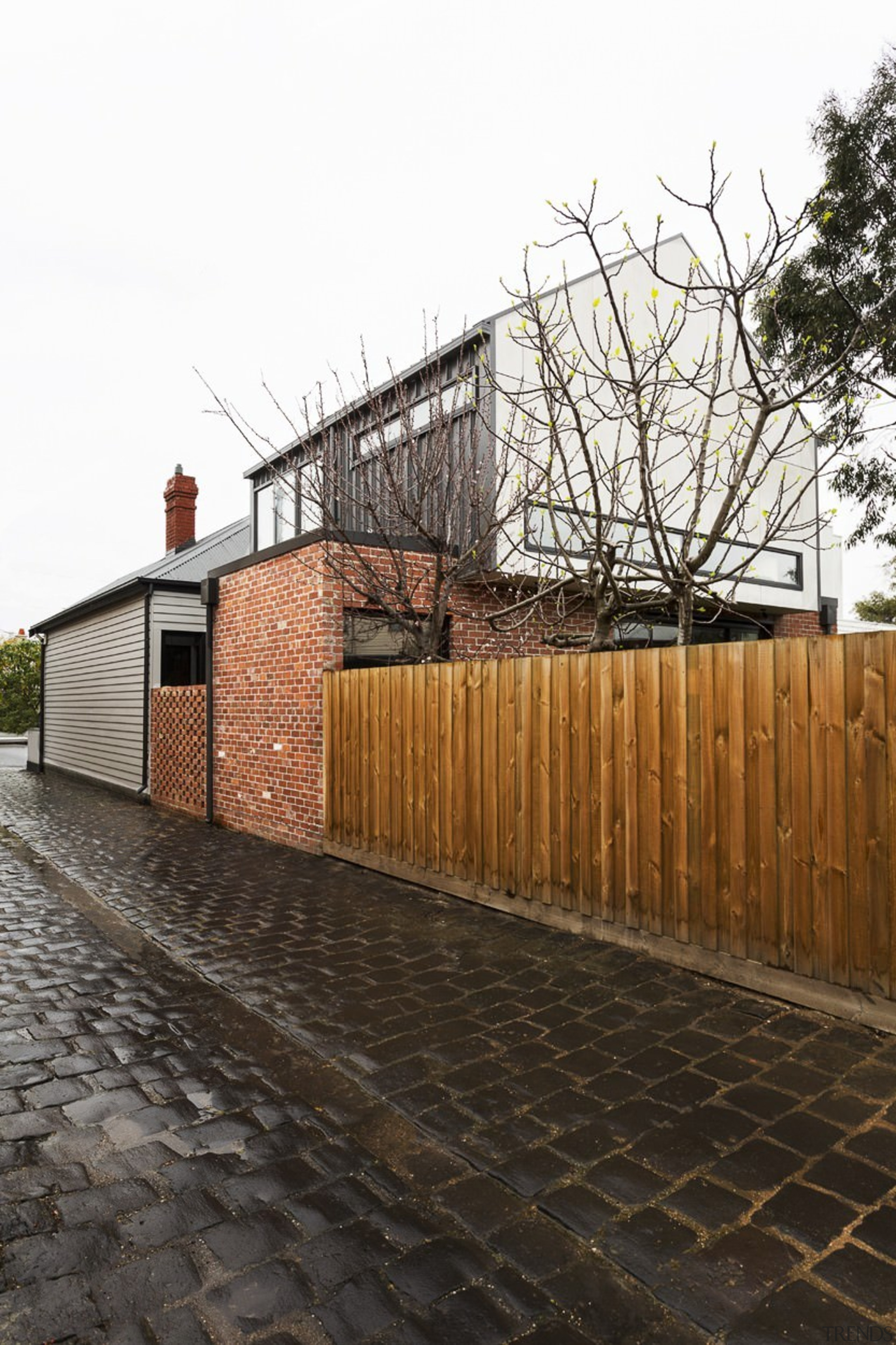 Wood, brick and concrete make for interesting exterior architecture, building, facade, fence, house, iron, outdoor structure, property, residential area, tree, walkway, wall, wood, white, black