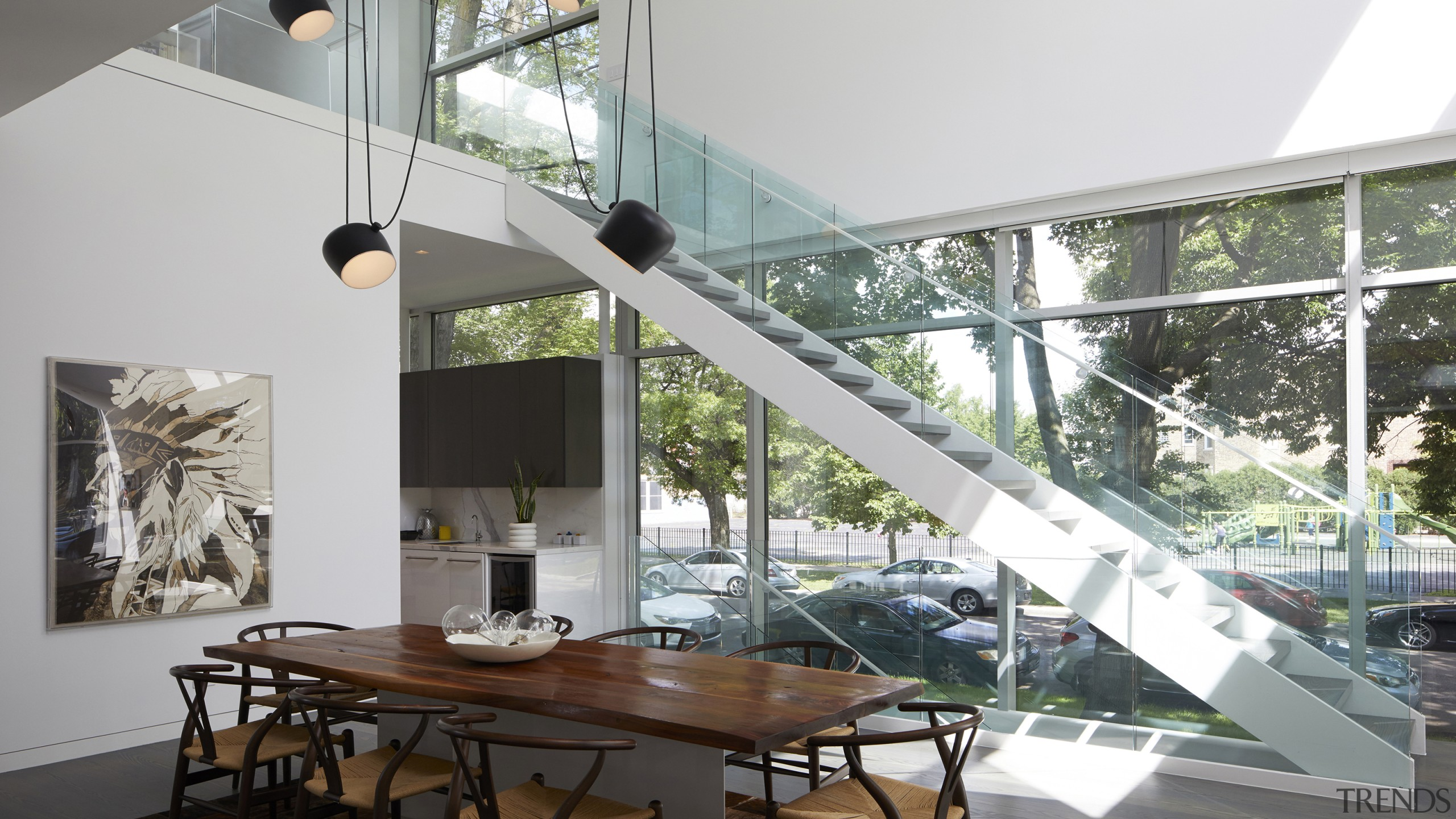 An open riser steel and glass staircase connects architecture, building, ceiling, daylighting, design, dining room, floor, flooring, furniture, glass, home, house, stairs, staircase, interior design, lighting, living room, loft, property, real estate, room, shade, table, window, gray, white