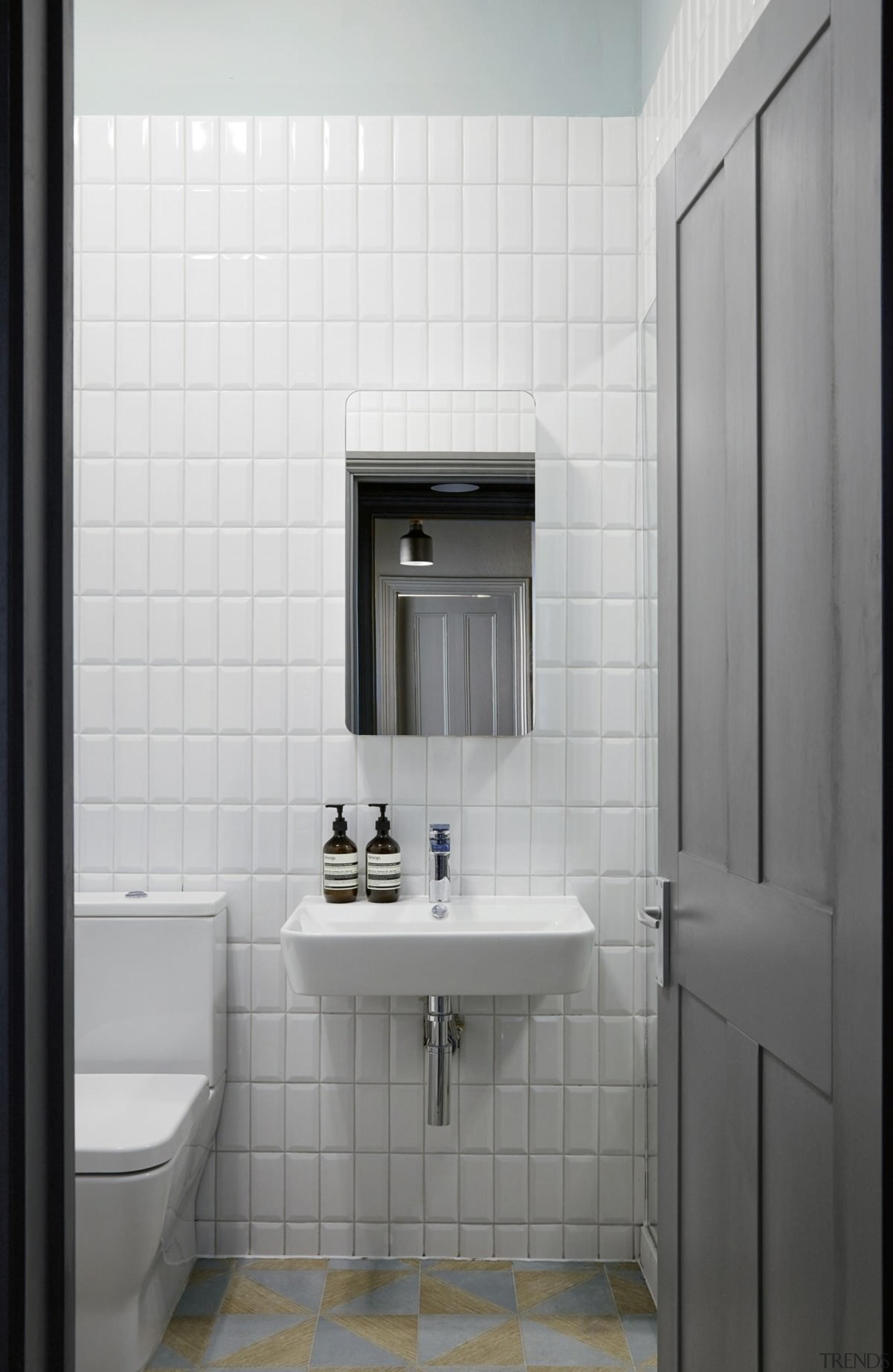White tiles keep the bathroom feeling open - bathroom, bathroom accessory, bathroom cabinet, floor, interior design, plumbing fixture, product design, room, sink, tile, gray