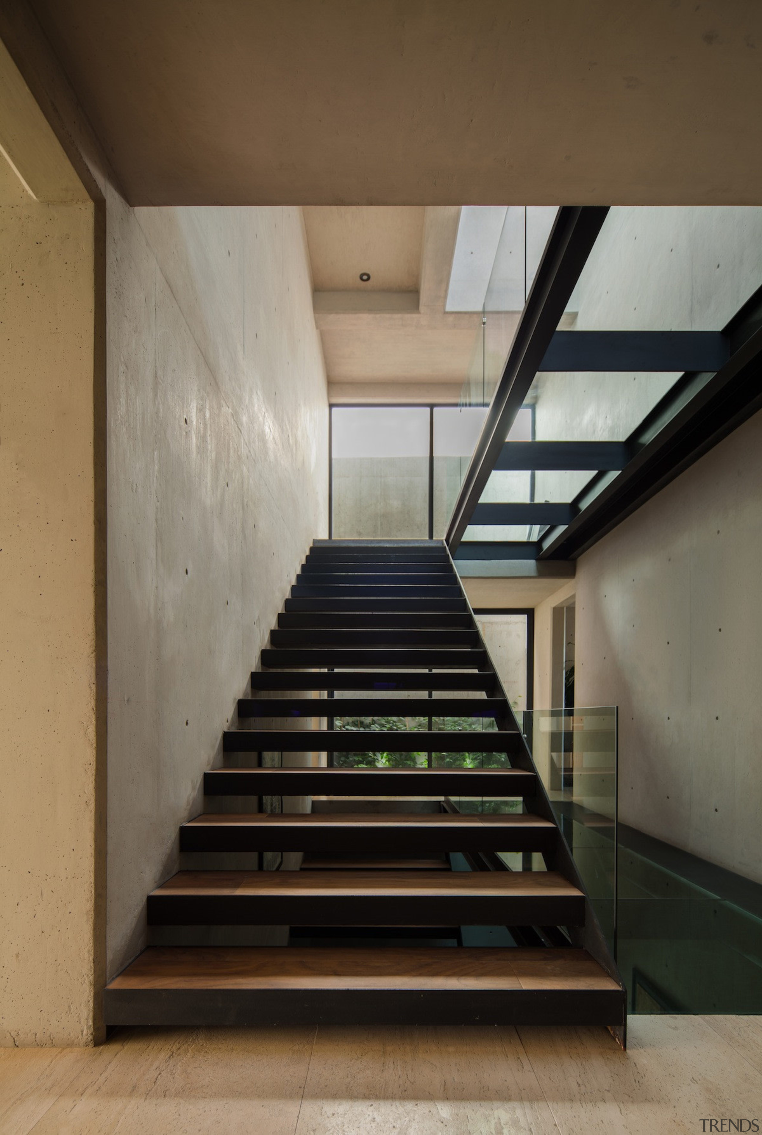 A glass walkway runs above the staircase - architecture, daylighting, handrail, house, interior design, stairs, black, brown, gray