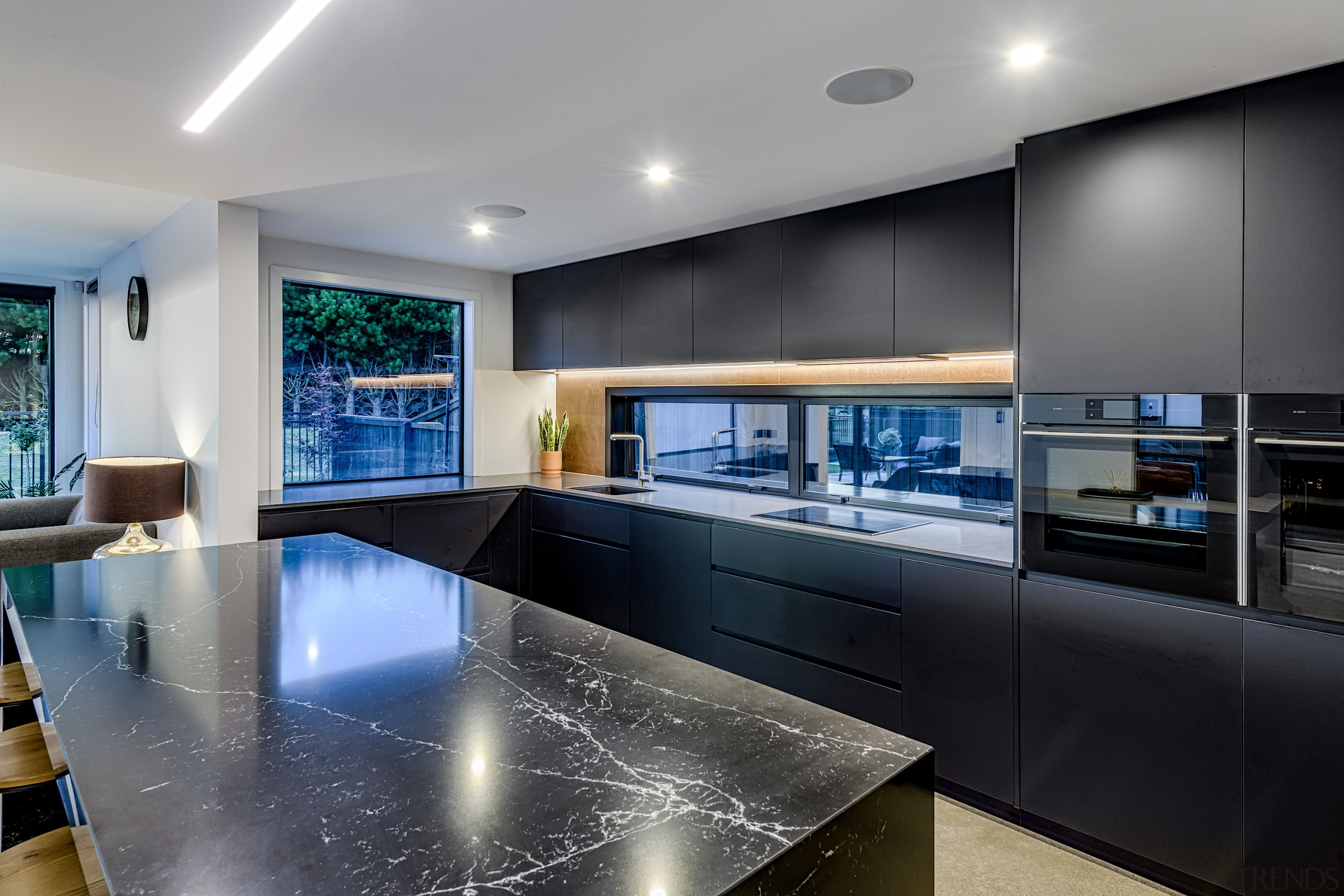 To make the island a standout feature, Kirsty architecture, building, cabinetry, ceiling, countertop, design, floor, flooring, furniture, glass, home, house, interior design, kitchen, light fixture, lighting, living room, property, real estate, room, table, gray, black