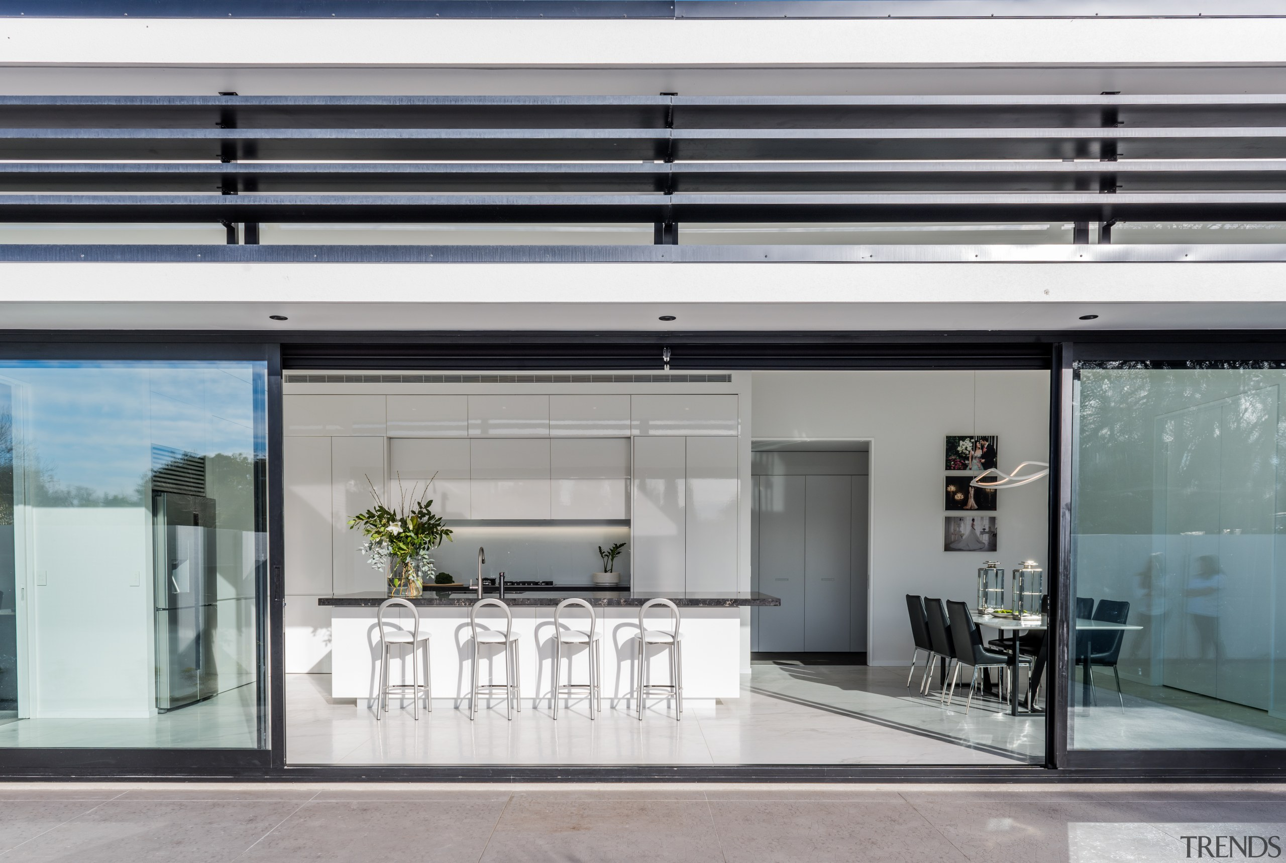 With handleless cabinetry closed, this pristine white entertainer's door, glass, house, interior design, window, gray