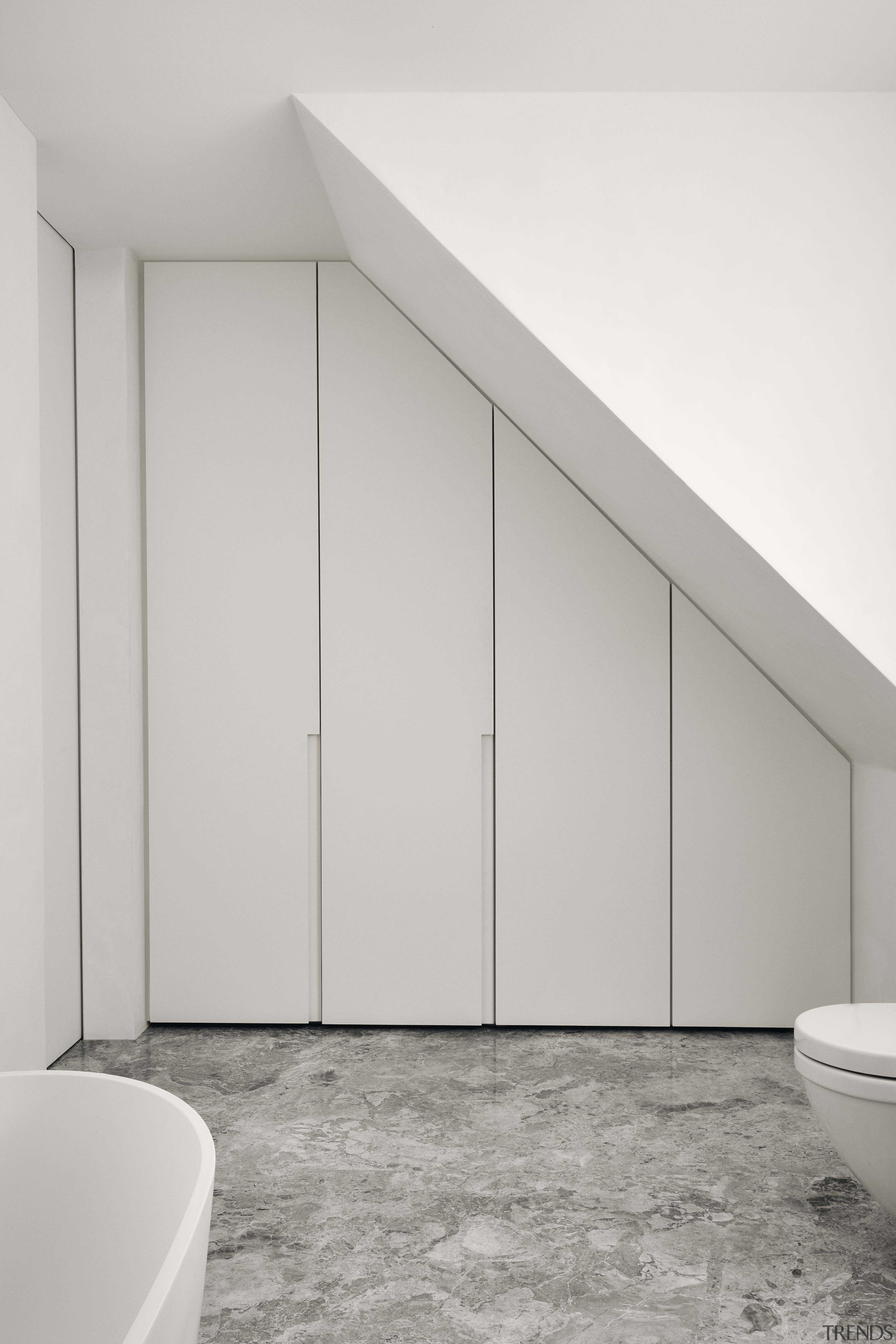 Bathroom cabinetry mirrors the slanting shower stall on