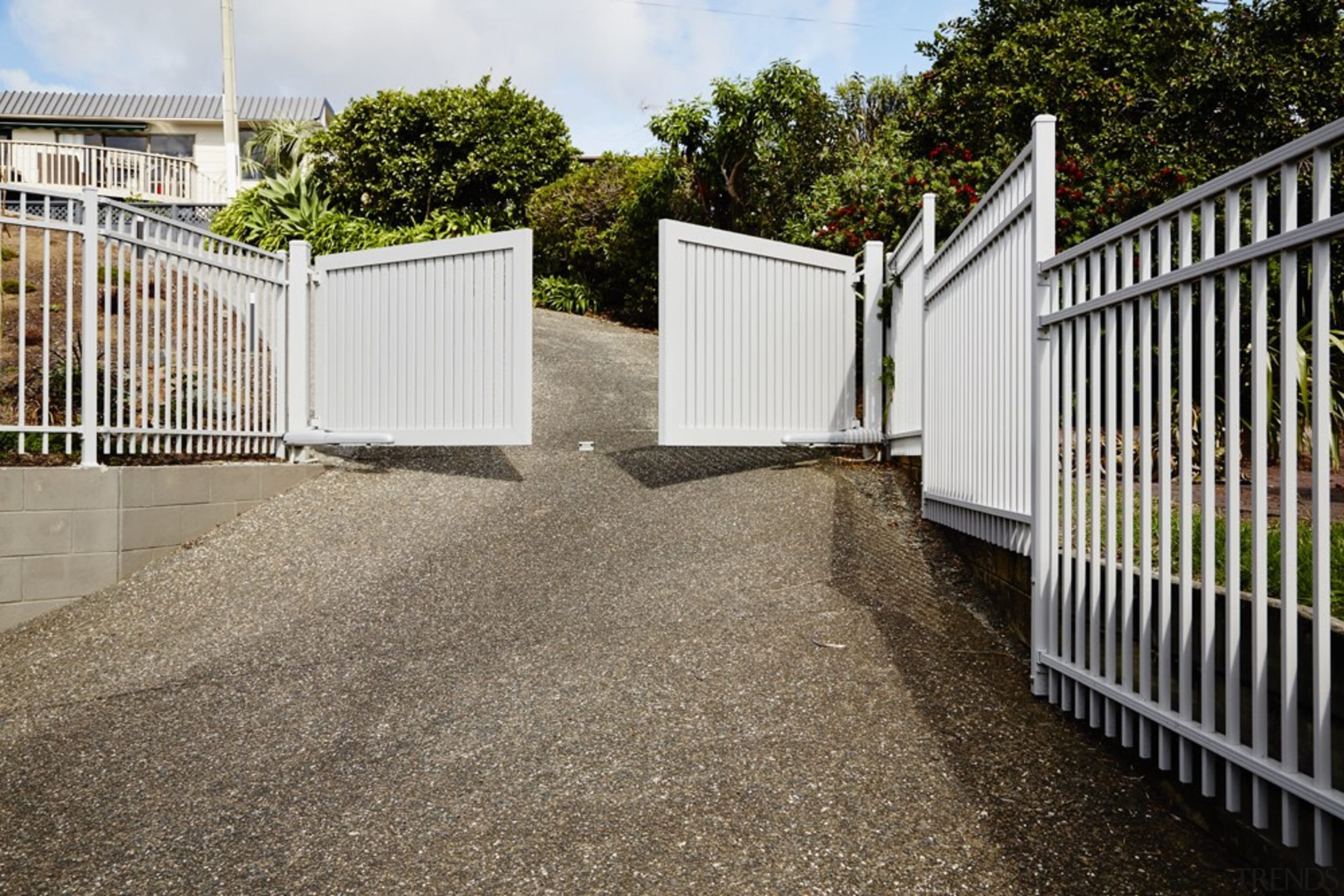 The gates are automated so they can be driveway, fence, gate, home, home fencing, outdoor structure, picket fence, property, real estate, residential area, walkway, gray