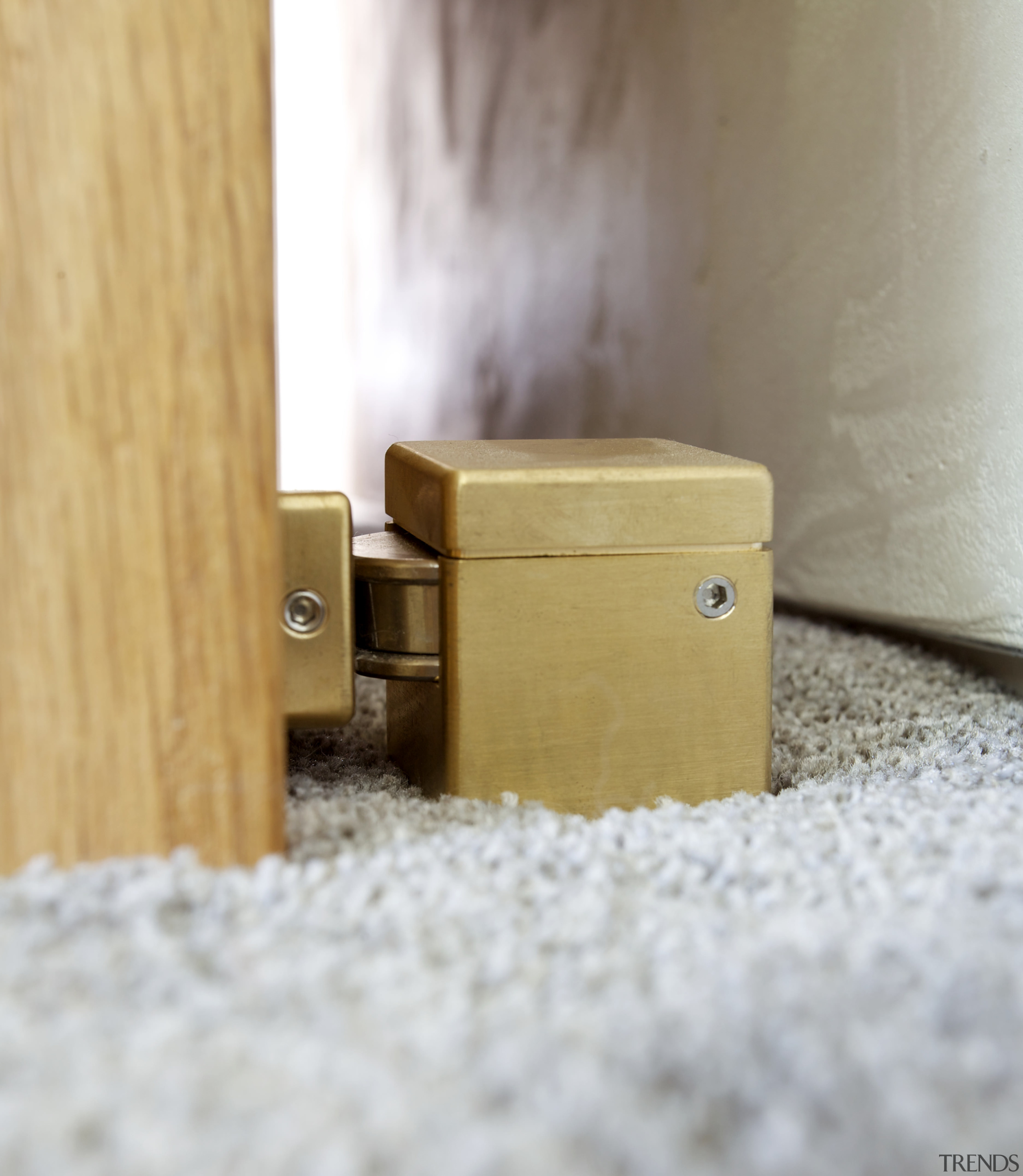 Magnetic brass doorstops by Chant contribute to the lock, product design, wood, gray