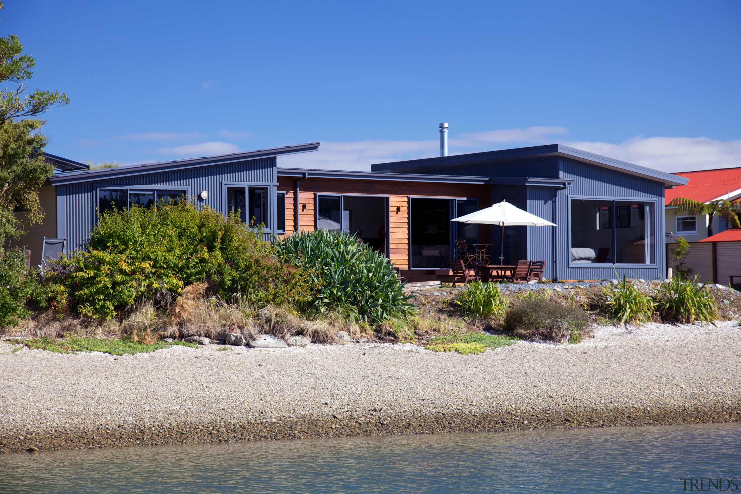 Nestled among the trees on the shoreline at architecture, cottage, estate, facade, home, house, property, real estate, residential area, villa, blue, gray