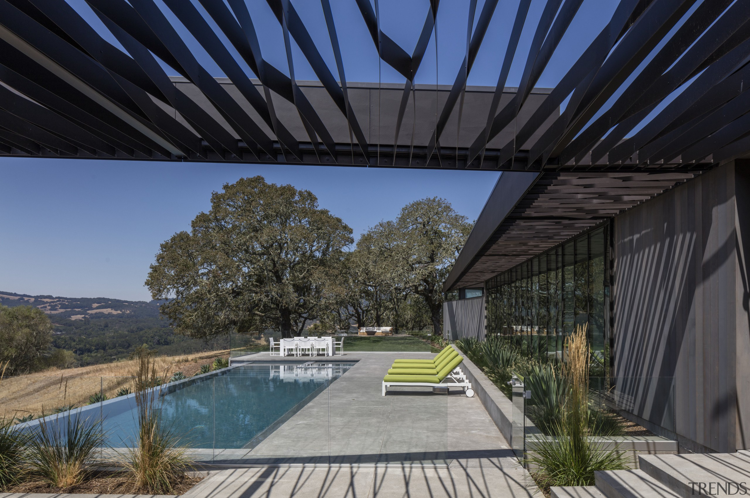 While the trellis running alongside the two wings architecture, estate, home, house, landscape, outdoor structure, plant, property, real estate, roof, sky, black