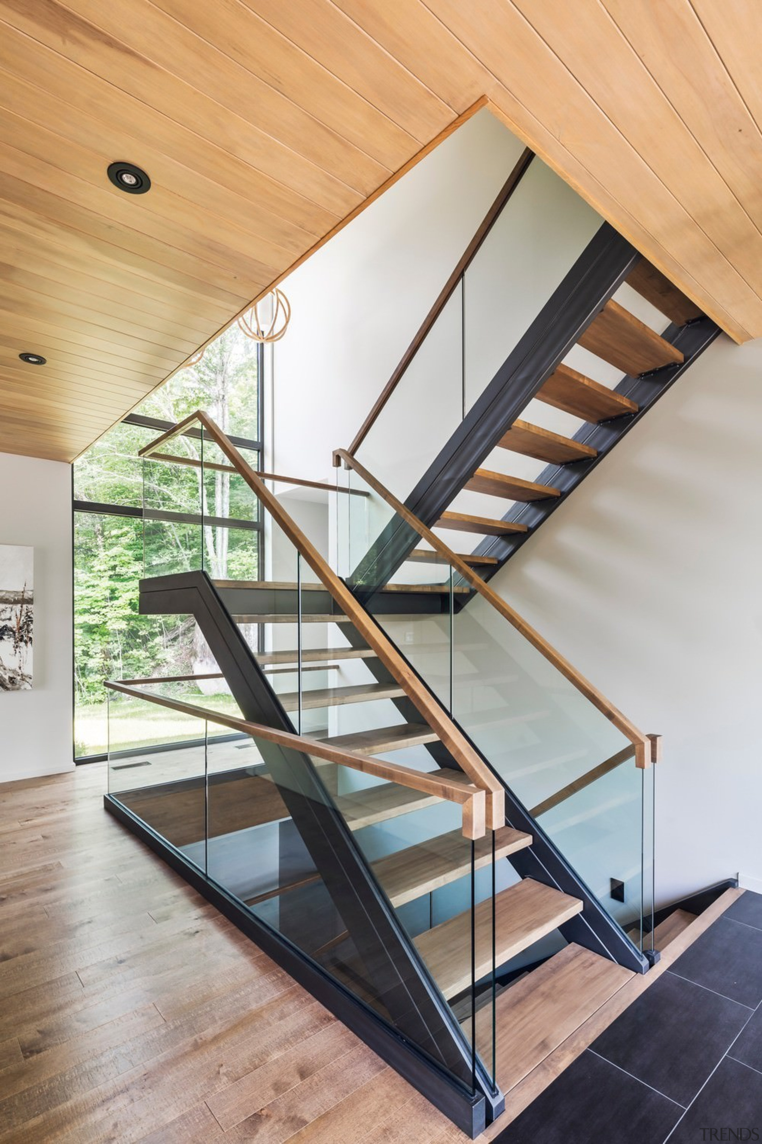 The feature staircase connects all levels of the architecture, daylighting, glass, handrail, house, interior design, product design, stairs, structure, wood, gray, orange