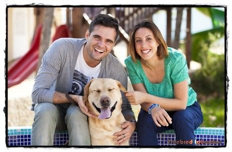 happy couple with labrador retriever