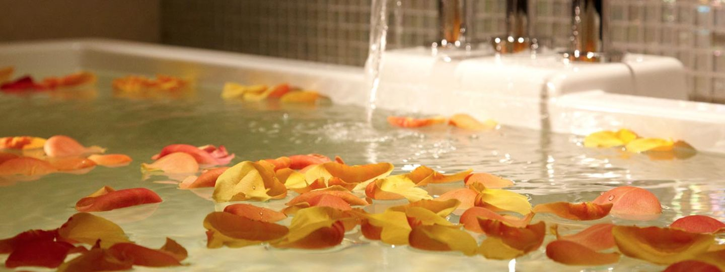 Bathtub Filled With Water and Flower Petals