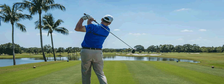 Golfer Swinging Club on Course