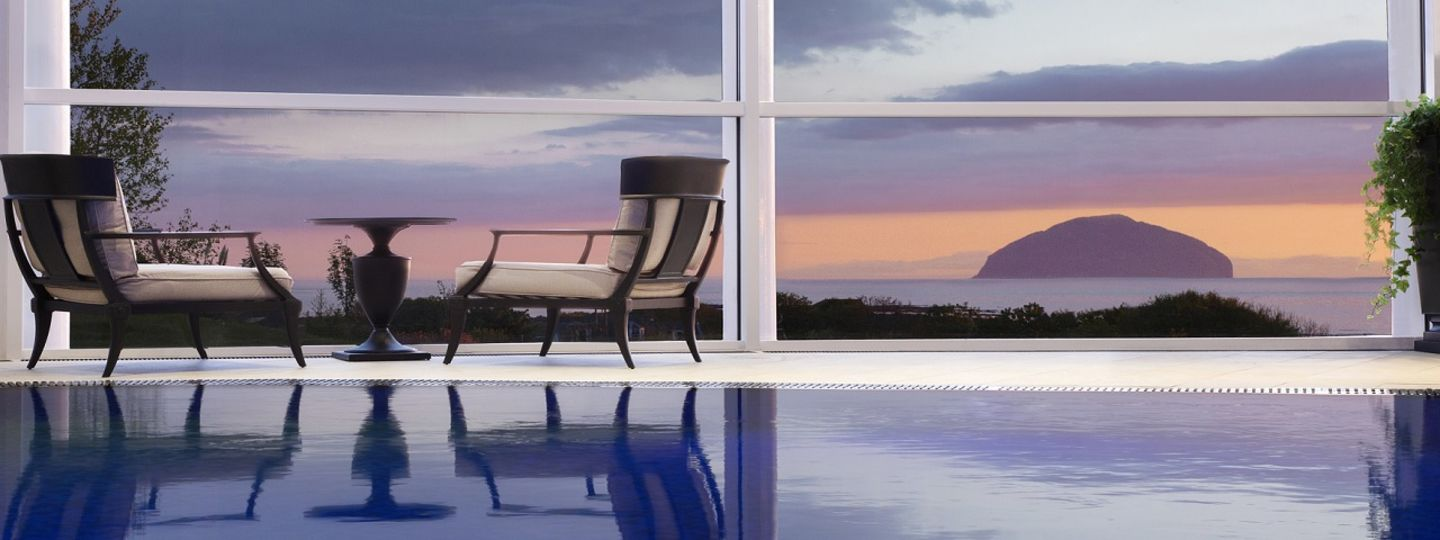 Trump Turnberry pool with chairs overlooking sunset and ocean