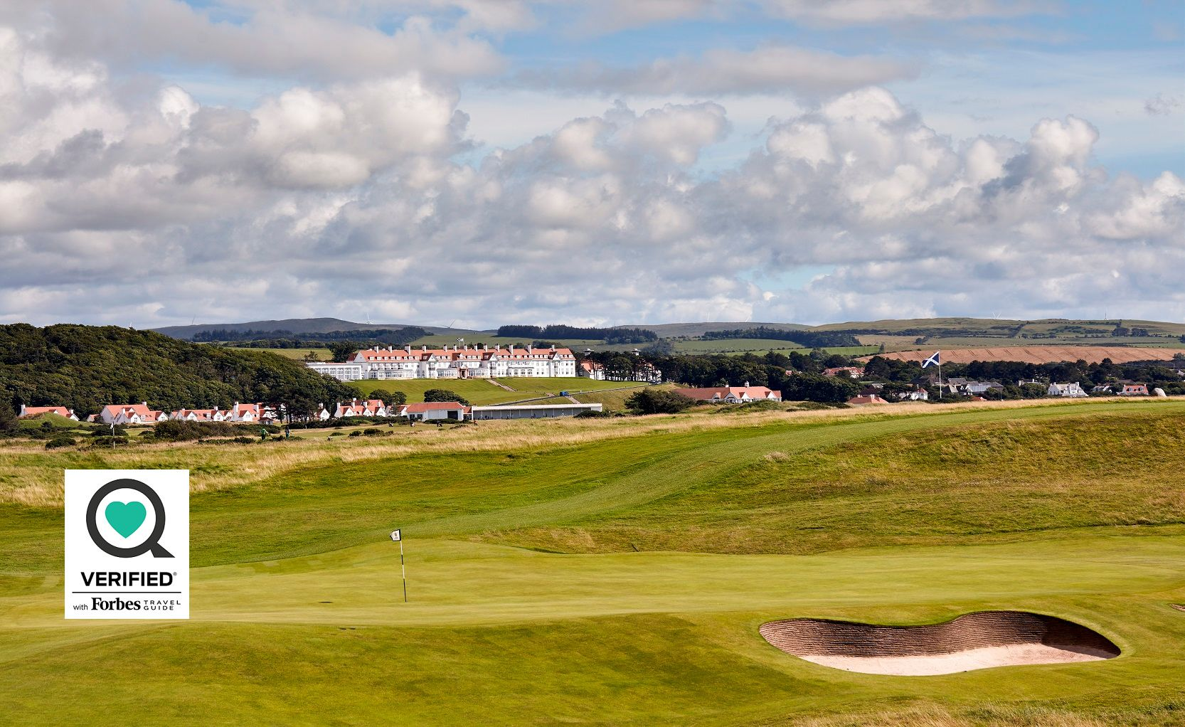 Trump Turnberry golf course with estate in background. Forbes Verified Sharecare logo overlaid on image