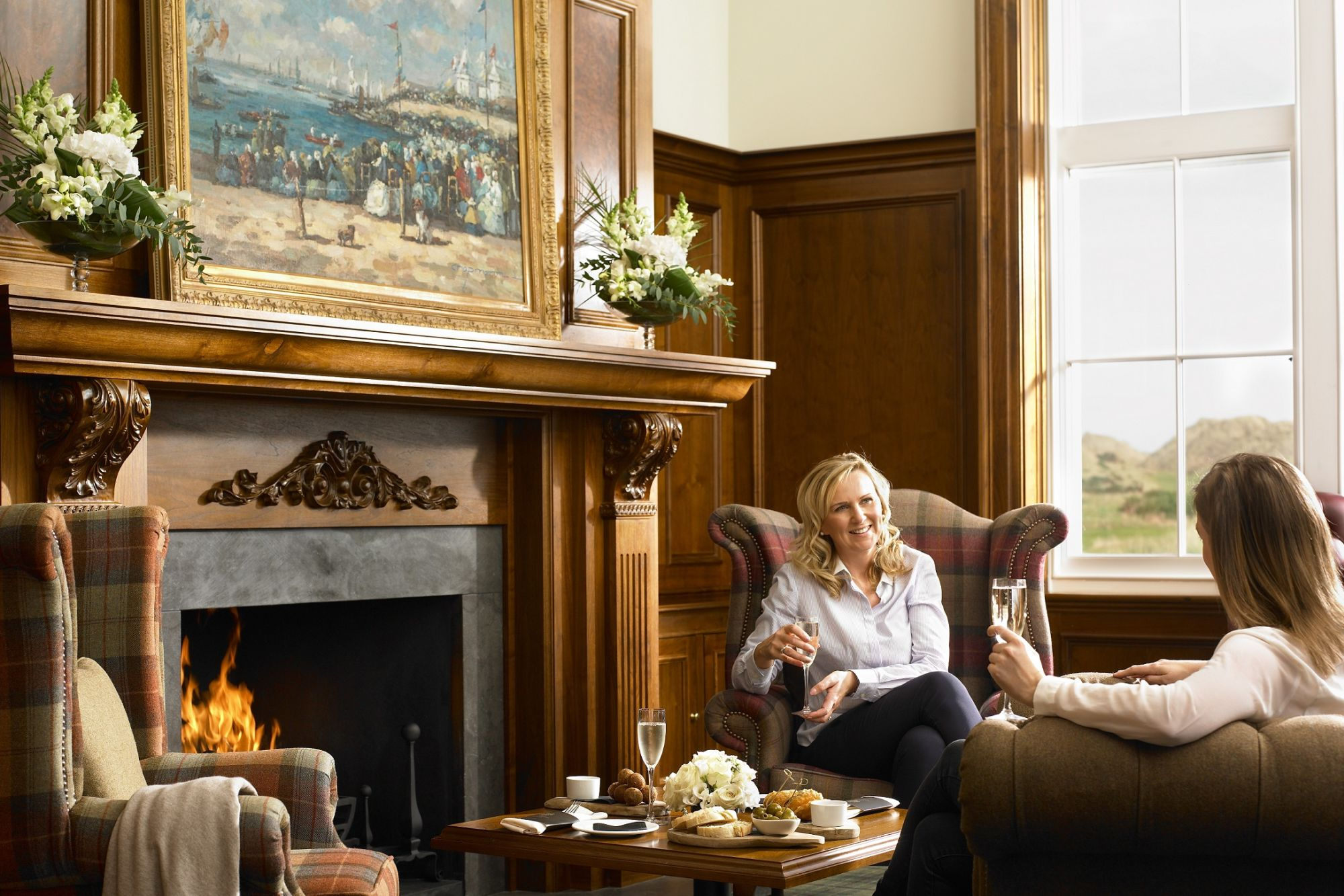 Two women drinking wine by fireplace at MacLeod House