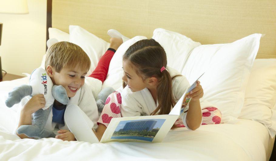 Children Reading in Hotel Bed