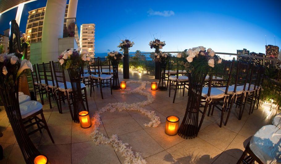 椅子が並べられ、花で飾られた夕暮れ時のウェディング・セレモニー会場