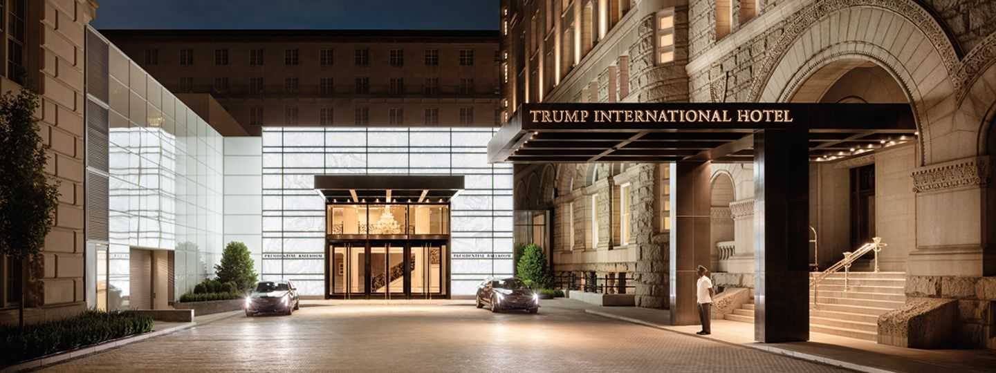 Hotel Entrance with Doorman and Cars at Night