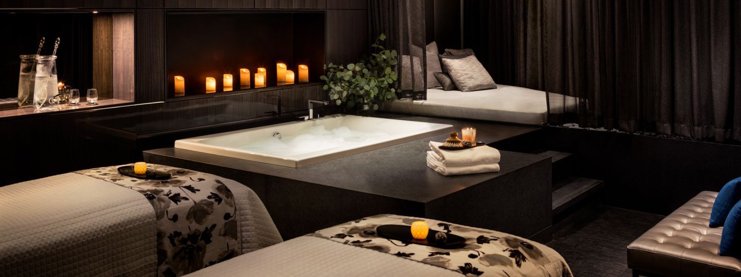 hotel spa area with beds, tub