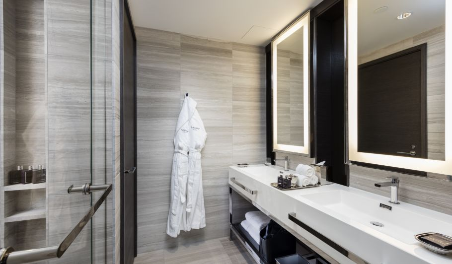 hotel interior bathroom with bathrobe on hanger, 2 sinks