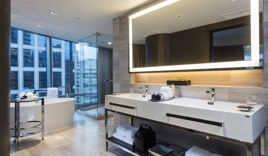 hotel interior bathroom with mirror, sinks, city view