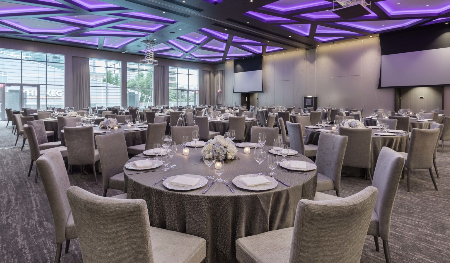 hotel interior banquet room with oval tables, chairs