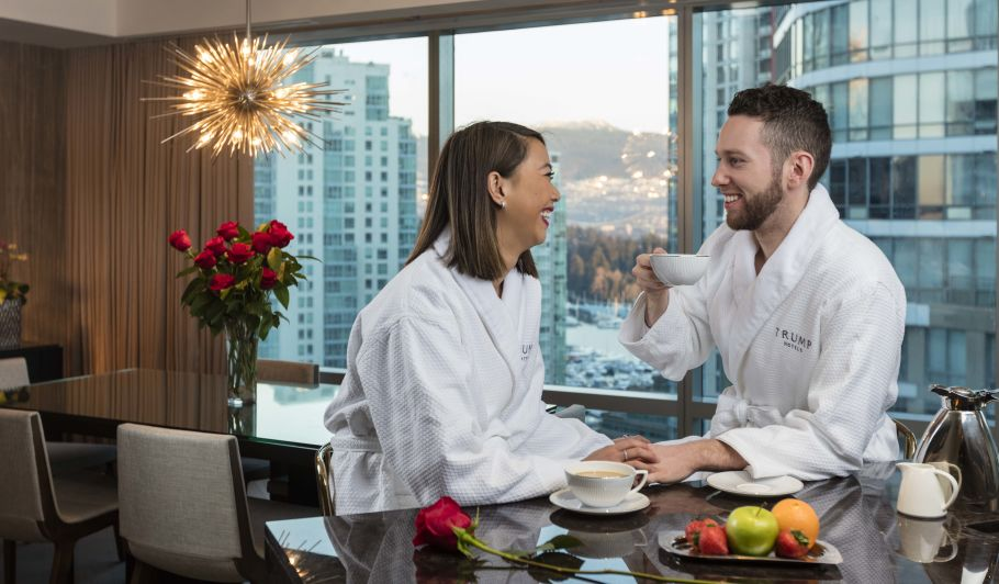 couple in bathrobes drinking coffee in hotel room