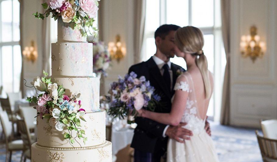 Bride and Groom Kissing Behind Wedding Cake