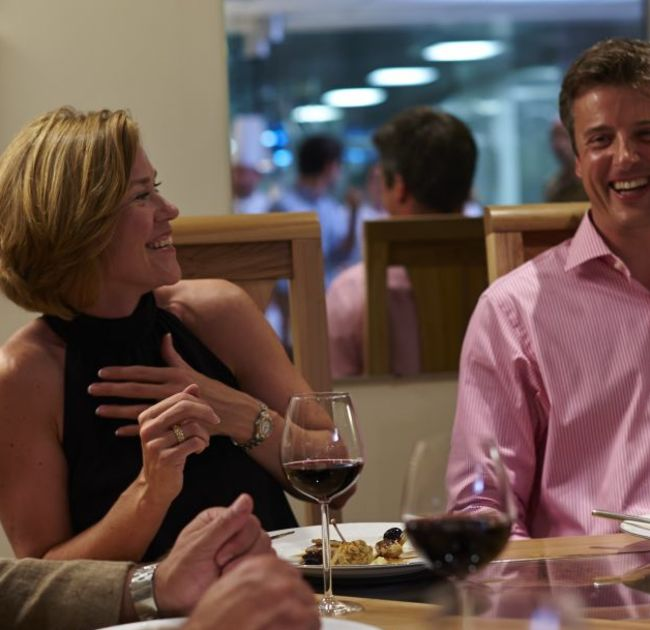 Woman and Man Laughing at Dinner Table