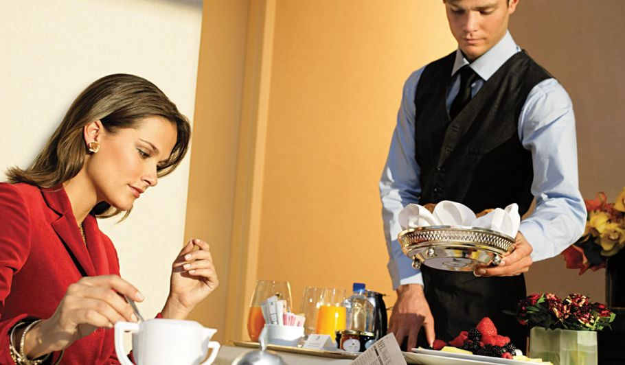 woman in hotel room eating room service