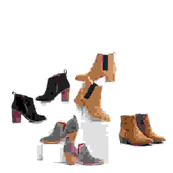 Four pairs of women's booties in brown, grey and black tones stacked on white boxes on a white background.