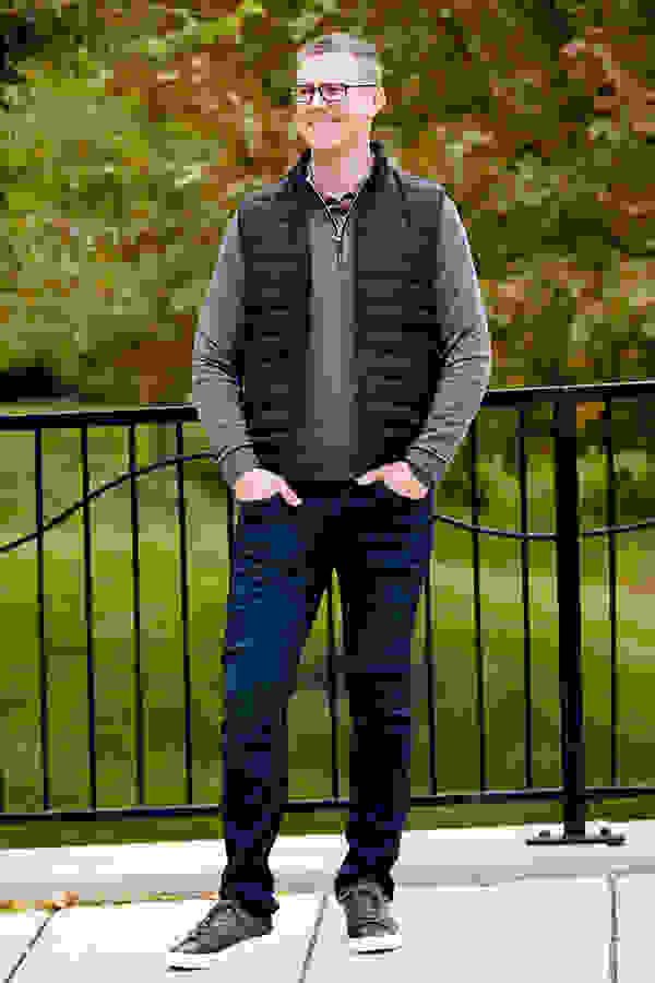 A man wearing stylish fall clothes standing in a park during the autumn.