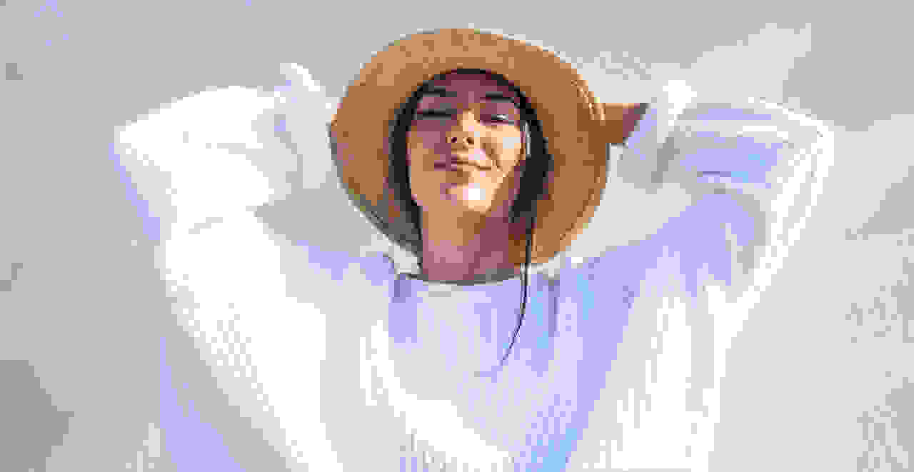 A women in a straw hat and white lightweight sweater