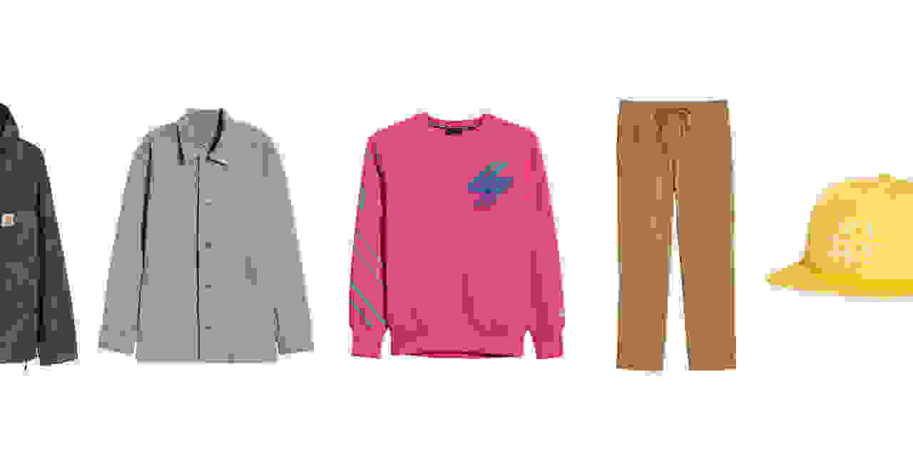 An assortment of men's clothing including a purple pullover, grey jacket, pink sweatshirt, brown pants and yellow hat.
