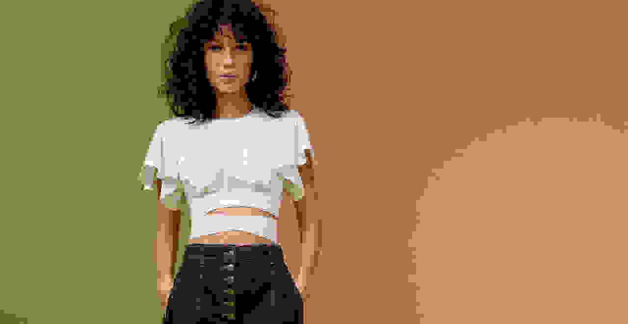 Woman in a white top with cutouts at the midriff.