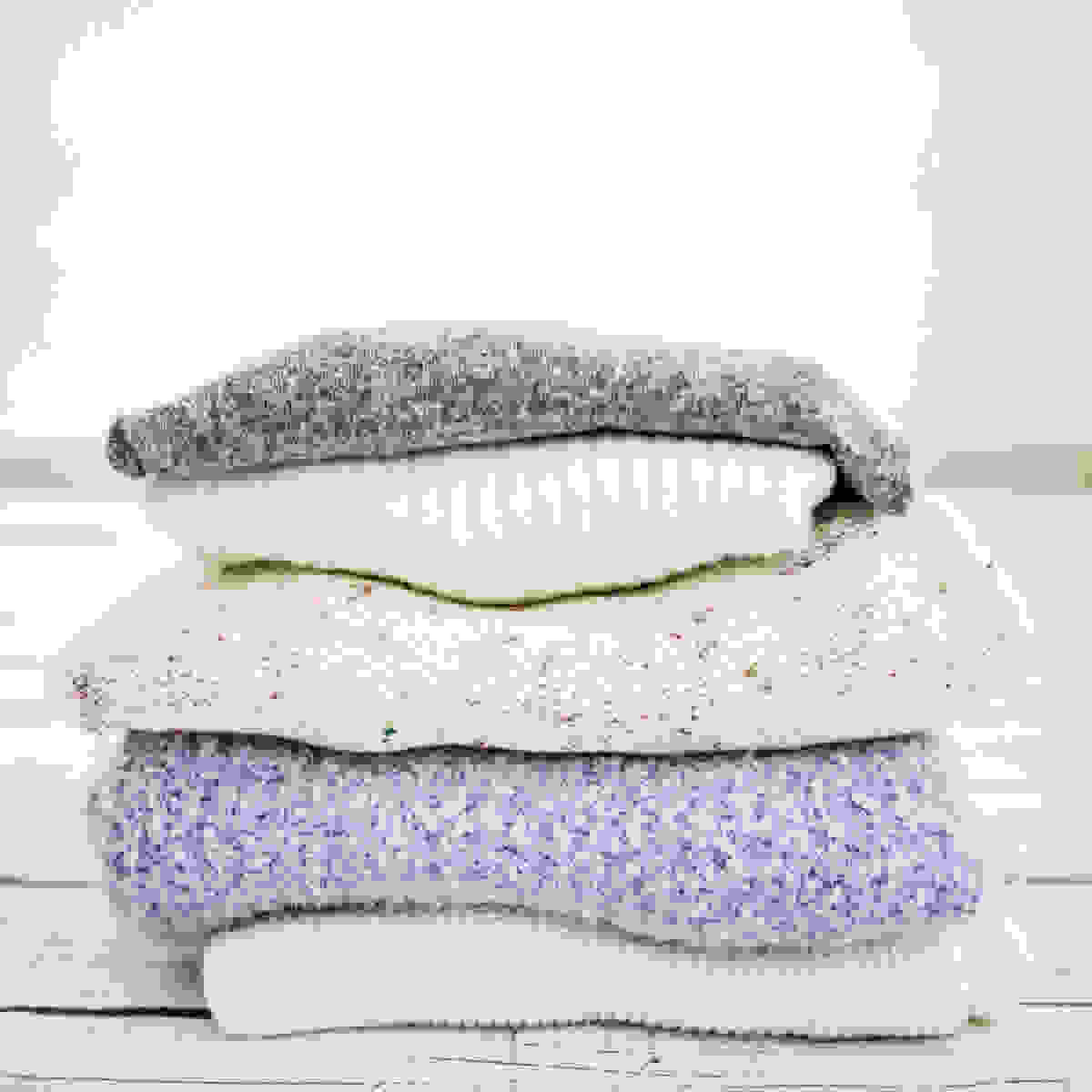 Stack of women's sweaters folded neatly on white wood background.