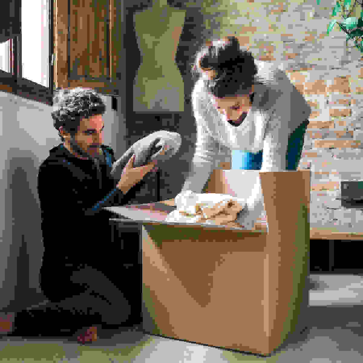 A man and woman placing seasonal clothes in a cardboard box for storage.