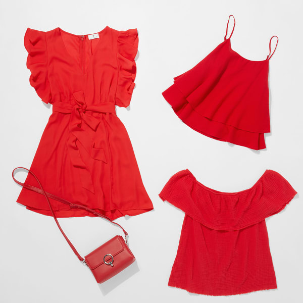 Three articles of red clothing - a ruffled dress, a flowing tank, an off the shoulder blouse - and a red satchel purse lain flat on a white background.