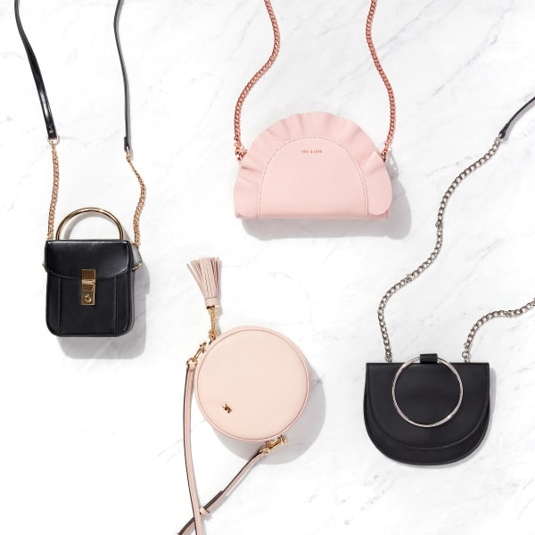 Four mini hand bags - two pink and two black - laid flat on a marble background.