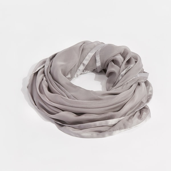 A sheer purple scarf draped casually in a pile on a white background.
