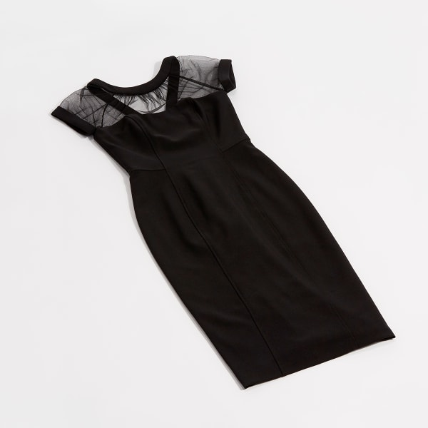 A little black dress with sheer panels over the shoulders laid flat on a white background.