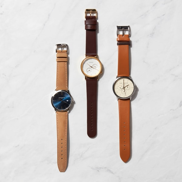 Three watches with brown leather bands oriented vertically and laid flat on a marble background.