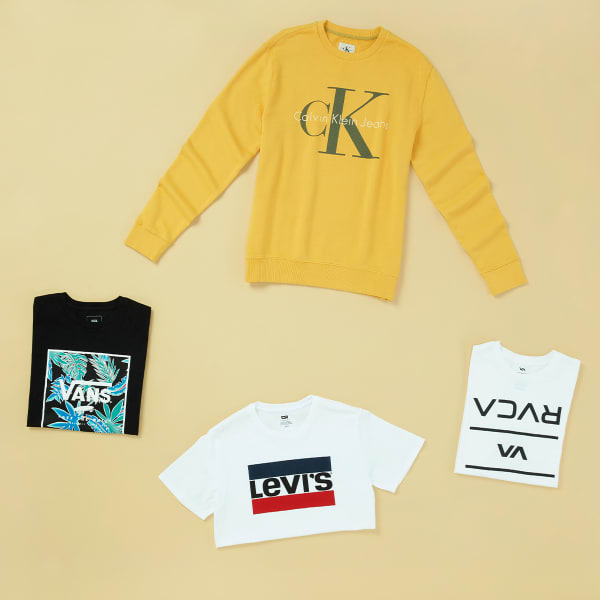Four articles of men's clothing featuring logos - a Levi's tee, Calvin Klein sweatshirt, Vans tee, and a RVCA tee - a hat, Timberland shorts, Nike shorts, and Nike sneakers - laid flat on a light yellow background.