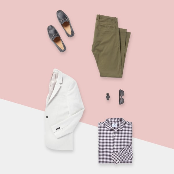Six articles of men's fashion - a sport coat, pair of chinos, plaid shirt, loafers, sunglasses and a watch - laid flat on an off-white background with light pink diagonal running through the composition.