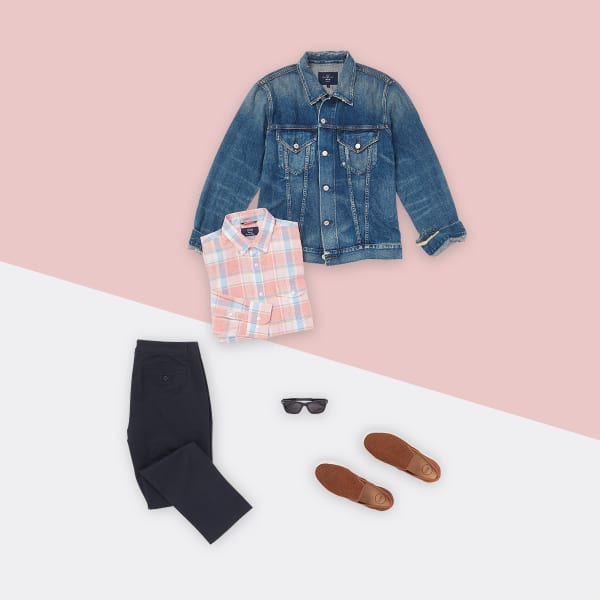 Five articles of men's fashion - a plaid shirt, a denim jacket, a pair of chinos, slip-on shoes, and sunglasses - laid flat on an off-white background with light pink diagonal running through the composition.