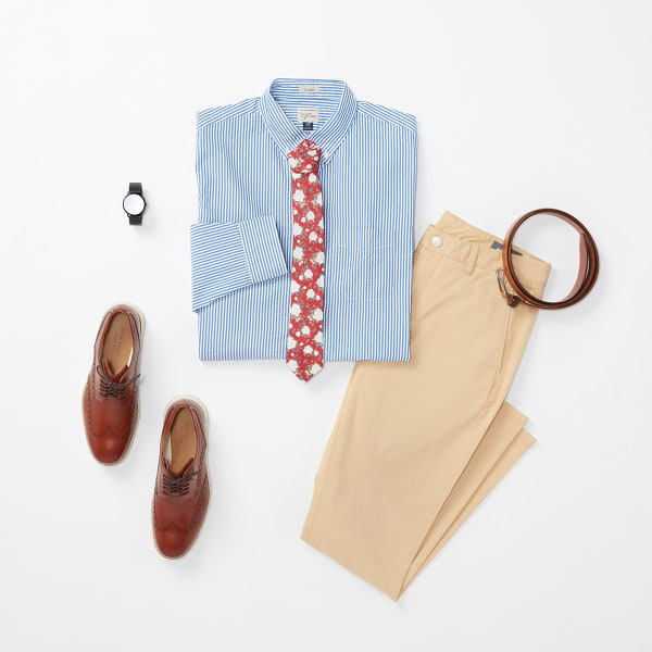 Six men's fashion items - a blue plaid dress shirt, a pair of chinos, a red tie, a pair of brown dress shoes, a watch and a tan belt - laid flat on a white background.