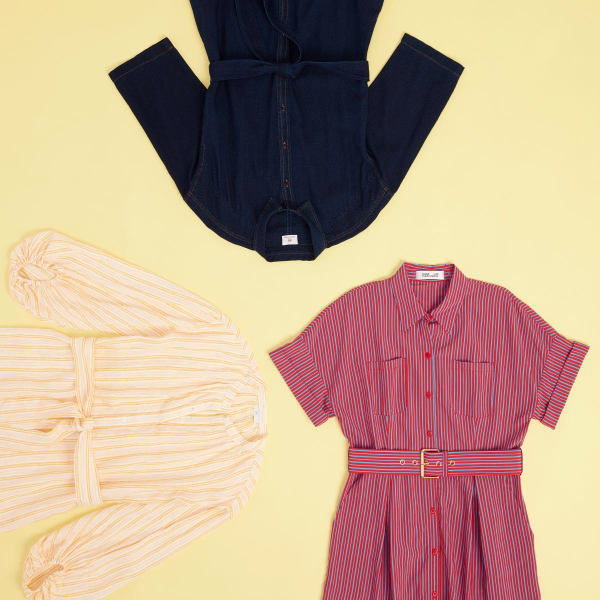 Three women's shirt dresses with sleeves extended to show detail laid flat on a dusty yellow background.