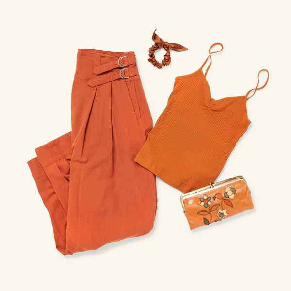 Three items of women's clothing - a silk hair tie, a pair of pleated trousers, and a knit tank - and a leather crossbody purse laid flat on a white background.